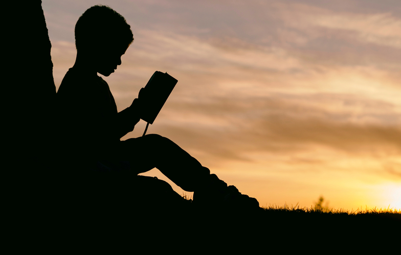 Extra_large_canva_-_silhouette_of_a_kid_reading_at_sunset