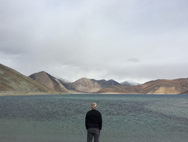 Small_canva_-_man_traveler_standing_alone_on_cliff_lake_and_foggy_mountains_on